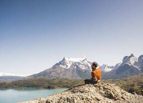 Hiker resting in mountainscape at Lago Pehoe in Torres del Paine National Park, Patagonia, Chile - UUF20240