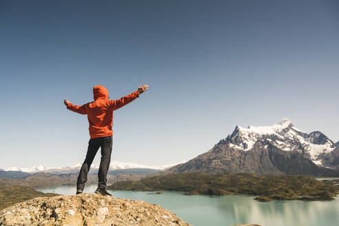 Hiker raising his arms in mountainscape at Lago Pehoe in Torres del Paine National Park, Patagonia, Chile - UUF20243
