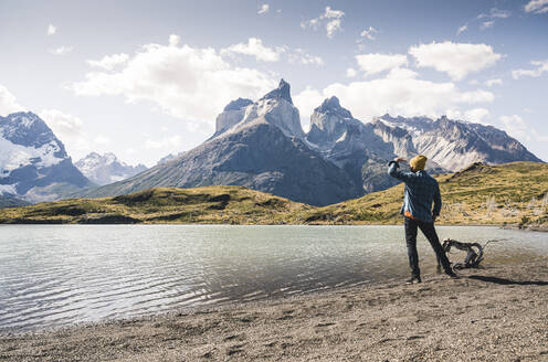 Hiker in mountainscape at lakeside in Torres del Paine National Park, Patagonia, Chile - UUF20246