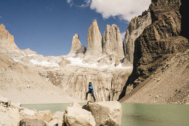 Hiker jumping in mountainscape at lakeside at Mirador Las Torres in Torres del Paine National Park, Patagonia, Chile - UUF20273