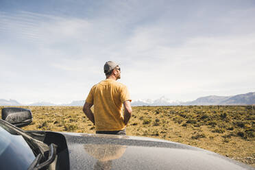 Rear view of man at car in remote landscape in Patagonia, Argentina - UUF20276