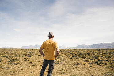 Rear view of man standing in remote landscape in Patagonia, Argentina - UUF20279