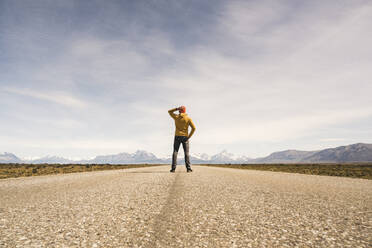 Man standing on a road in remote landscape in Patagonia, Argentina - UUF20288