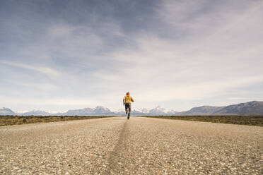 Man running on a road in remote landscape in Patagonia, Argentina - UUF20291