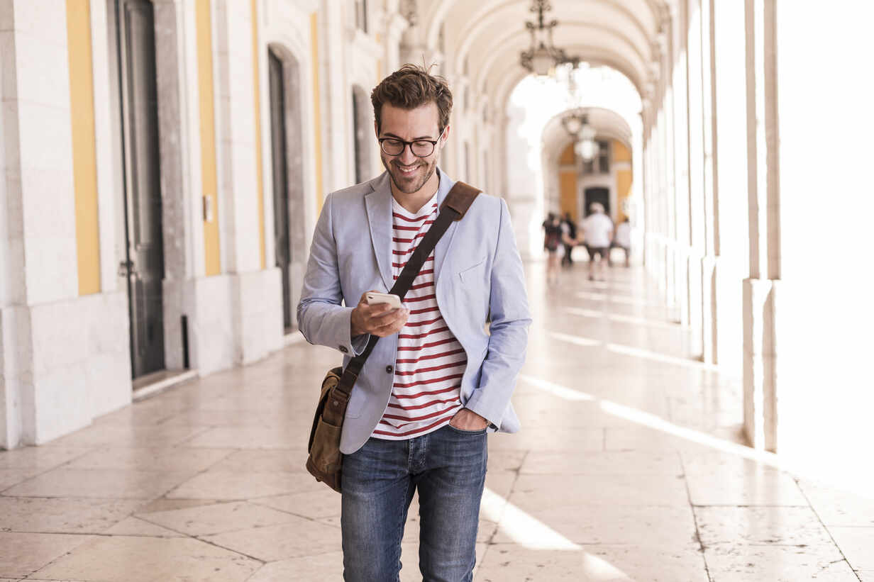 Smiling young man using smartphone in the city, Lisbon, Portugal - UUF20344 - Uwe Umstätter/Westend61