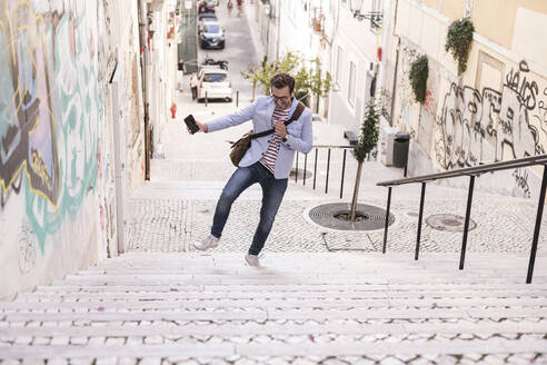 Carefree young man on stairs in the city, Lisbon, Portugal - UUF20353