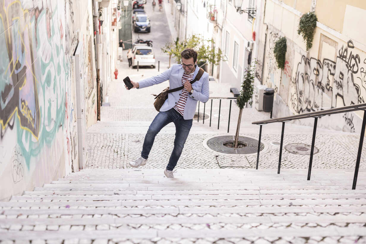 Carefree young man on stairs in the city, Lisbon, Portugal - UUF20353 - Uwe Umstätter/Westend61