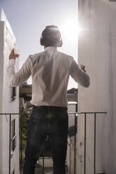 Rear view of young man with headphones on a balcony - UUF20356