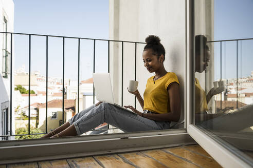 Young woman sitting on a balcony with laptop and coffee cup - UUF20362
