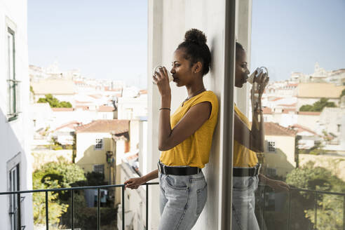 Young woman drinking coffee on a balcony - UUF20365