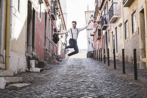 Carefree young man jumping in the old town, Lisbon, Portugal - UUF20368