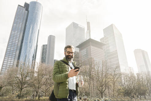 Man using smartphone in front of skycrapers, Frankfurt, Germany - AHSF02493