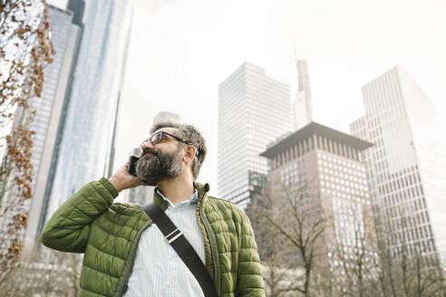 Man on the phone in front of skycrapers, Frankfurt, Germany - AHSF02502