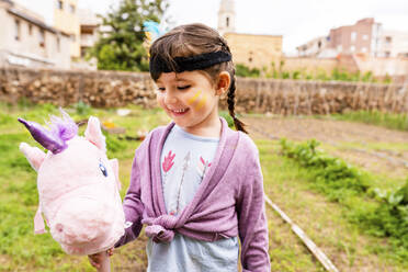 Portrait of girl with braids and feather headdress with a pink unicorn - GEMF03641