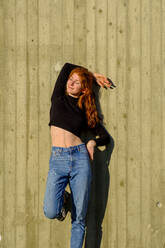 Portrait of smiling teenage girl with eyes closed leaning against concrete wall enjoying sunlight - LBF03057