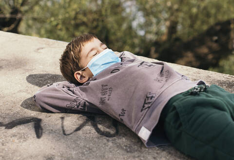 Portrait of boy with eyes closed wearing protective relaxing on a wall - MOMF00865