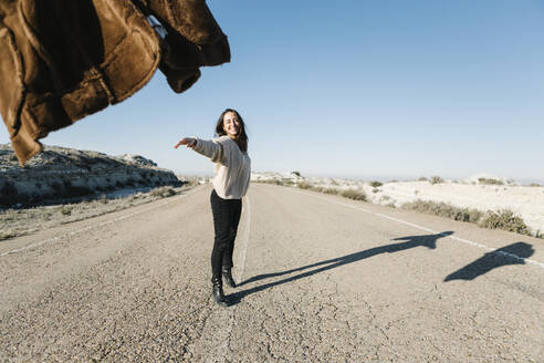 Smiling woman throwing jacket while standing on road at desert against clear sky - XLGF00127