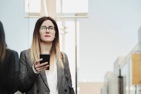 Portrait of young businesswoman with smartphone looking at distance - MRRF00014