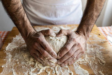 Man's hands shaping heart on dough ball - WPEF02885