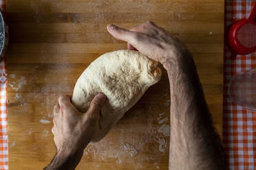 Man's hands kneading dough, top view - WPEF02888