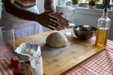 Crop view of man spreading flour on dough ball in the kitchen - WPEF02891