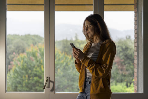 Smiling redheaded woman standing in front of window looking at cell phone - AFVF06211