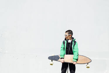 Boy with skateboard and headphones standing in front of white wall looking at distance - JCMF00696