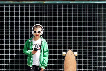 Portrait of boy with skateboard listening music with headphones and smartphone - JCMF00699