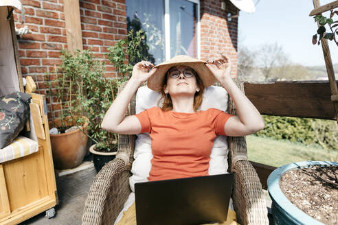Mature woman with laptop relaxing on terrace - KMKF01314
