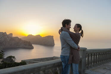 Couple standing on terrace by sunset hugging each other, Cap Formentor, Mallorca, Spain - DIGF10356