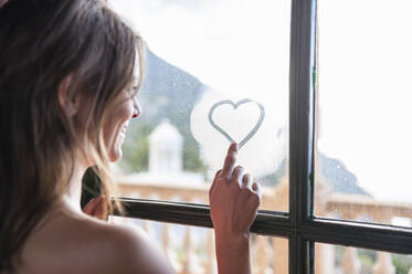 Happy woman drawing heart with herfinger on fogges windowpane, Mallorca, Spain - DIGF10362