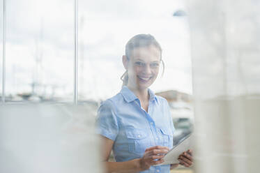 Portrait of smiling woman with digital tablet behind windowpane at marina, Mallorca, Spain - DIGF10365