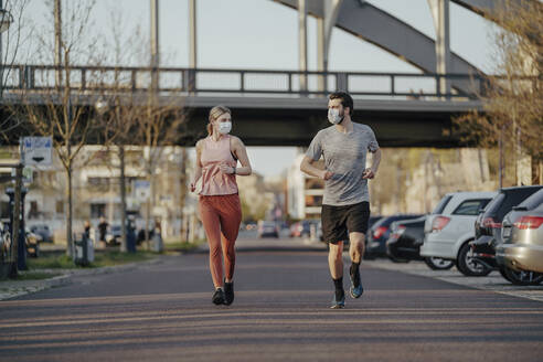 Young couple jogging on road in city during coronavirus - STDF00230