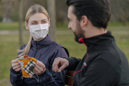 Young woman giving face mask to man while sitting at park during quarantine - STDF00242
