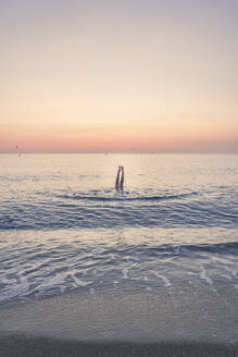 Teenage girl swimming in Mediterranean sea with feet up against sky during sunrise - FVSF00263