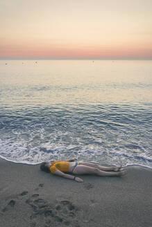 Full length of teenage girl lying on shore at beach during sunrise - FVSF00266