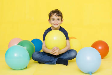 Portrait of smiling cute boy sitting with colorful balloons against yellow background - JRFF04419