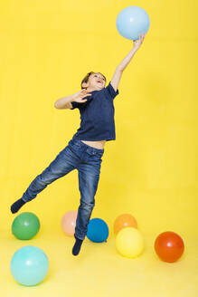 Full length of boy catching balloon while playing against yellow background - JRFF04422