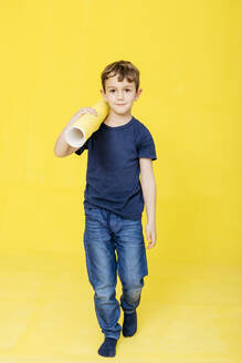 Full length portrait of cute carrying exercise mat while walking against yellow background - JRFF04425