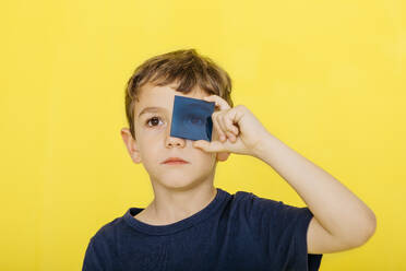 Close-up of cute boy holding blue acrylic glass against yellow background - JRFF04431
