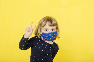 Portrait of cute blond girl wearing face mask and gesturing peace sign against yellow background - JRFF04434