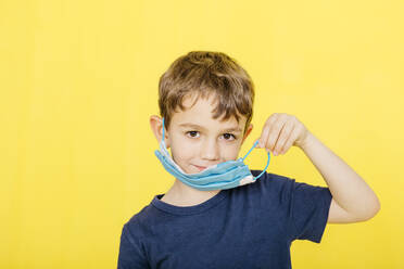 Portrait of smiling boy wearing face mask while standing against yellow background - JRFF04437