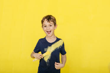 Portrait of cheerful boy playing with paintbrush while standing against yellow background - JRFF04440