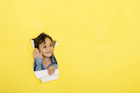 Smiling cute boy waving while looking away through torn yellow paper - JRFF04446