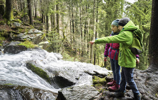 Boy and girl looking at waterfall in Northern Black Forest - DIKF00483