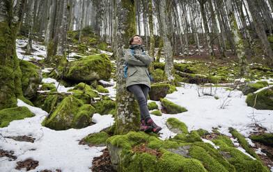Frau lehnt mit geschlossenen Augen an einer Buche im Frühjahr im Nordschwarzwald mit Schneeresten. Bannwald. Ruhe. Einsam. BW, D. - DIKF00486