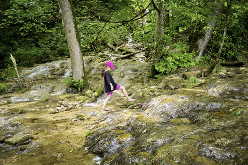 Full length side view of girl walking barefoot on natural stream in forest - DIKF00492