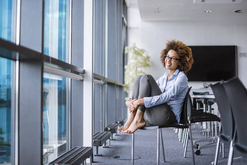 Smiling young businesswoman sitting at the window in conference room - DIGF10388