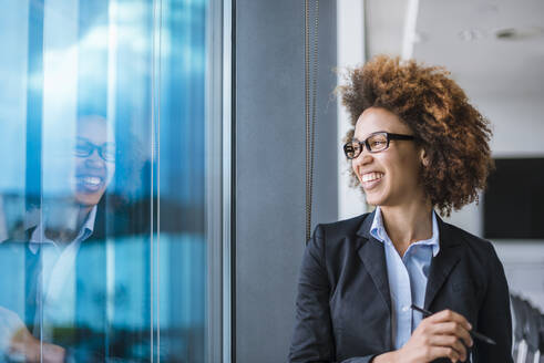 Portrait of happy young businesswoman in office looking out of window - DIGF10394