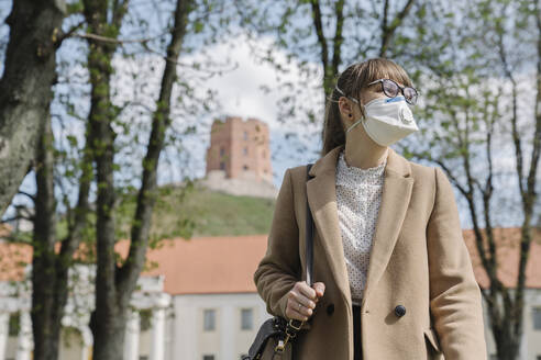 Woman wearing FFP2 mask looking sideways in the city - AHSF02512